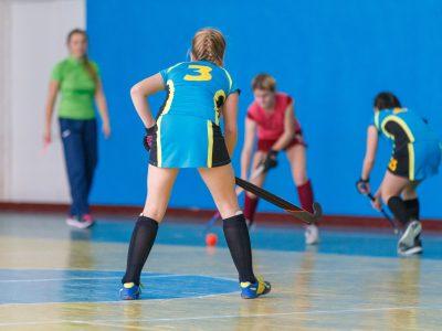Young girls playing indoor hockey. Indoor hockey training