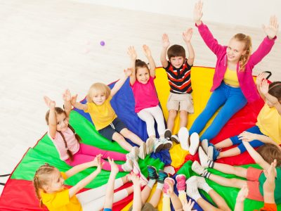 Portrait of young nursery teacher playing circle games with preschool children, sitting on rainbow parachute in gym